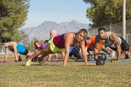 Cheerful blond fitness instructor leading group in push-ups photo
