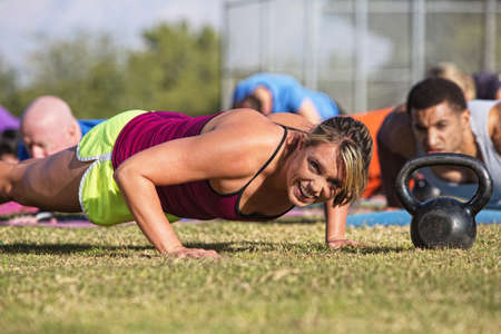 Embarrassed woman doing push-ups with group outdoors