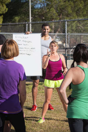 Two young fitness instructors explaining an exercise program photo