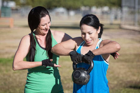 boot camp: Friendly fitness instructor helping student use kettle bell weight