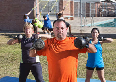 boot camp: Three adults exercising shoulder muscles with kettle bell weights