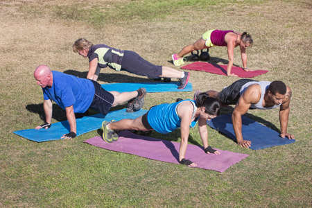 boot camp: Group of five people exercising in outdoor boot camp