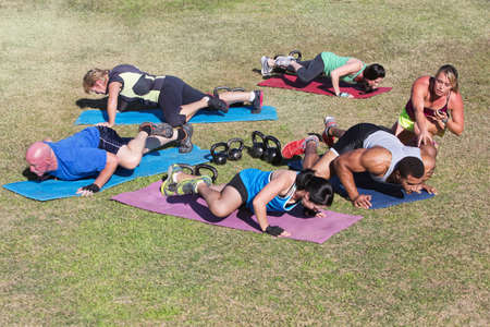 Bootcamp fitness trainer coaching diverse class outdoors