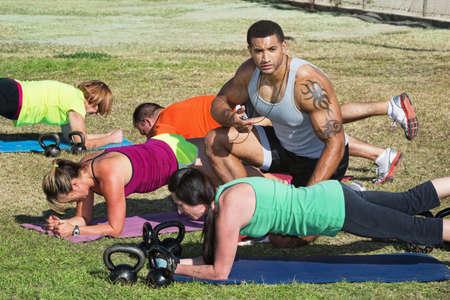 Instructeur met tattoo helpen bootcamp fitness studenten