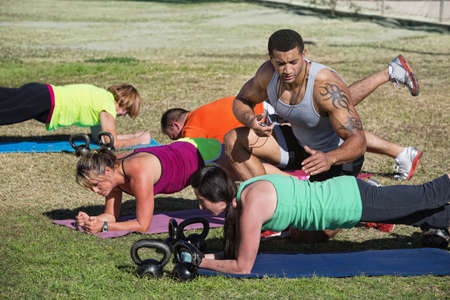 Muscular instructor with stopwatch helping students in fitness class photo