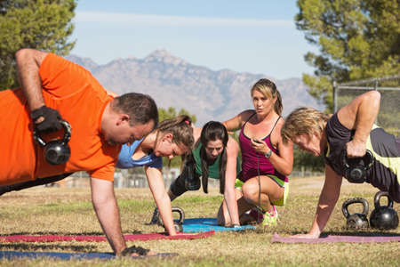 Instructor holding stopwatch while teaching bootcamp fitness photo
