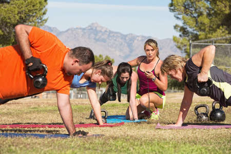 Young woman working with adults in boot camp fitness class photo