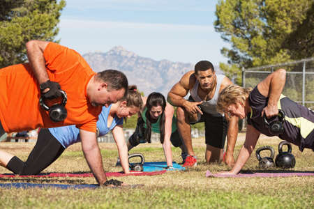 Male instructor training mature adults in boot camp fitness photo