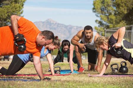 mujeres fitness: Instructor de la aptitud con las personas que ejercen en bootcamp aire libre Foto de archivo
