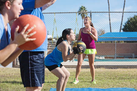 Bootcamp fitness instructor training adults with medicine ball