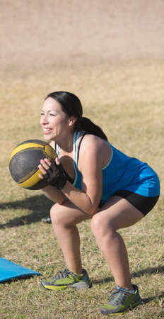 Smiling woman exercising with medicine ball outdoors photo