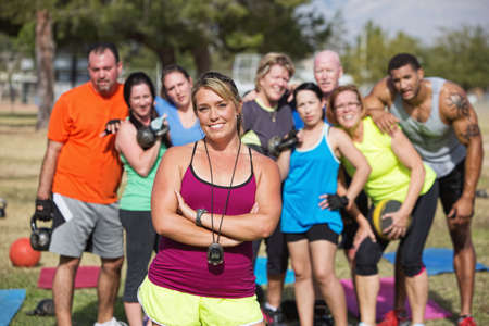Smiling confident trainer standing with fitness class