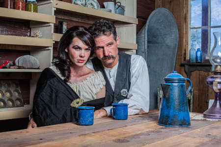 Serious looking western sheriff and woman pose inside of a house