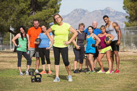 Serious mature woman with boot camp fitness class outdoors photo