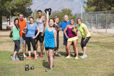 Happy woman lifting weights with group outdoors