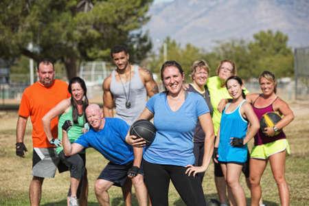 Smilng mujer y el campo de entrenamiento de grupo de fitness con balón medicinal Foto de archivo