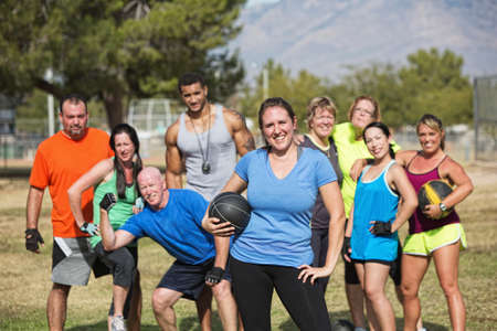 Smilng woman and boot camp fitness group with medicine ball