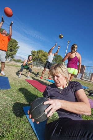 Diverse boot camp fitness class exercising outdoors photo