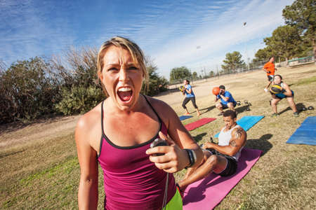 intimidating: Intimidating boot camp fitness trainer with adult class outdoors