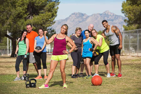 Serious female fitness instructor pointing to group of students photo
