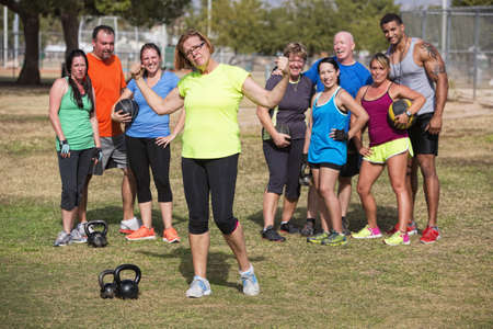 Confident mature woman flexing arms with fitness group standing photo