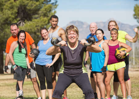 Grinning mature woman lifting kettle bell weights with group photo