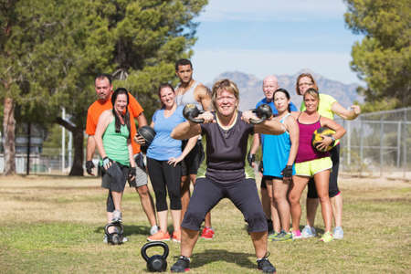 Smiling woman lifting kettle bell weights with group outdoors photo