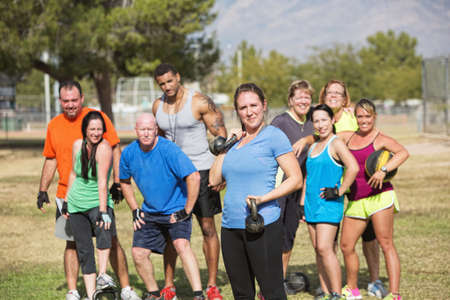 boot camp: Confident young lady with group lifting weights outdoors Stock Photo