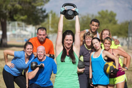 Group of people watching woman lifting kettle bell weights photo