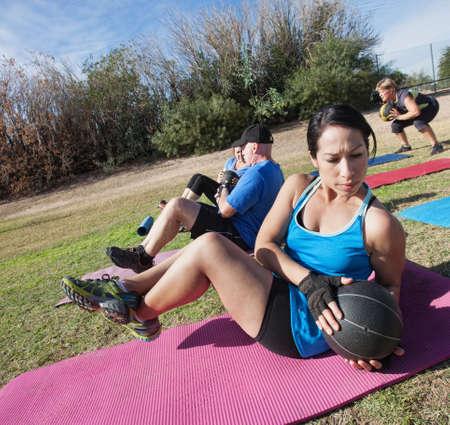 Aktive vielfältige Gruppe in Boot Camp Fitness-Klasse auf Matten