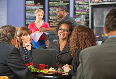 lunch meeting: Attractive white collar workers meeting for a working lunch Stock Photo