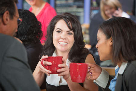 black man white woman: Grinning woman and coworkers with coffee in bistro