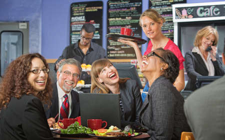 Coffee house barista serving laughing business people