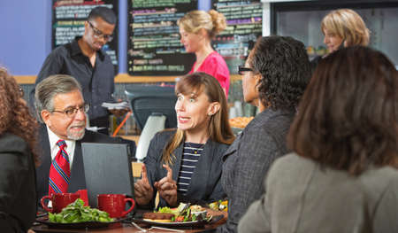 Excited business woman with coworkers and laptop in cafe photo