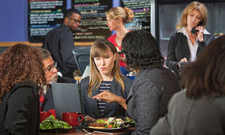 Skeptical woman with coworkers meeting during lunch photo