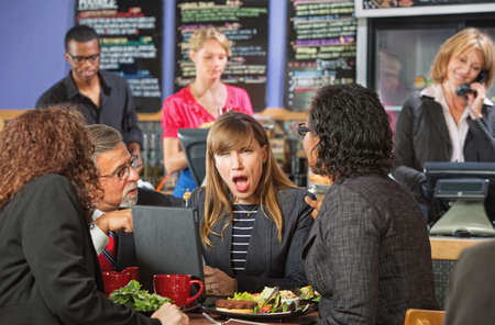 Shocked Hispanic woman in coffee house with coworkers photo