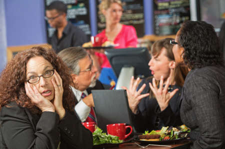 Bored woman with coworkers at lunch break photo