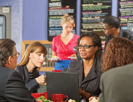 Business executive showing coworkers laptop in a coffee house photo