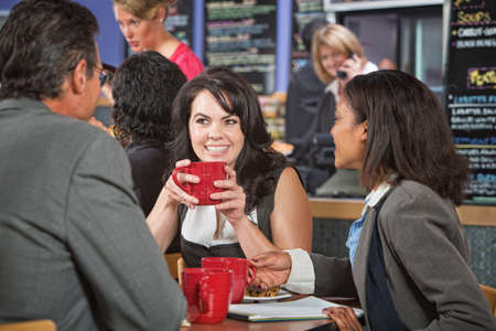 Attractive woman and coworkers with coffee cups in restaurant photo