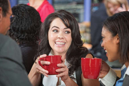 Happy adult female with coffee and friends in cafe photo