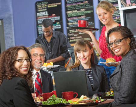 Happy group of people with laptop in cafe and barista photo