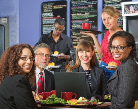 Smiling executives with attractive server in coffee house photo