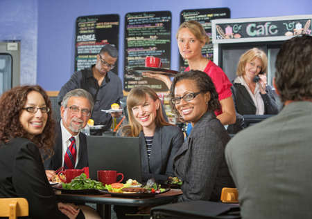 Barista serving diverse group of smiling business people photo