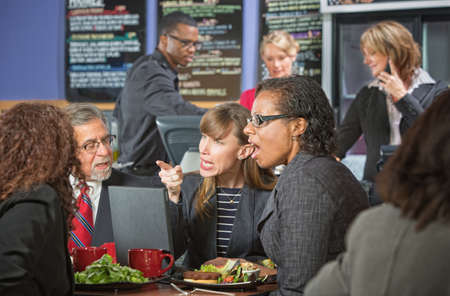 lunch meeting: Arguing business people with computer bickering over lunch Stock Photo