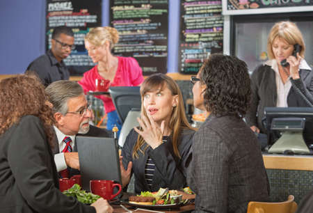 Surprised beautiful white collar worker with diverse group in cafe photo