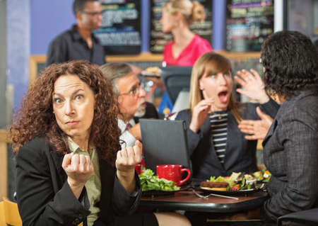 Angry woman with clenched fists at table with coworkers photo
