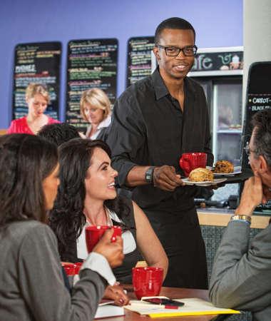 scone: Cheerful waiter bringing customers scones and coffee