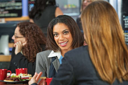 grinning: Happy female executives talking in a coffee house