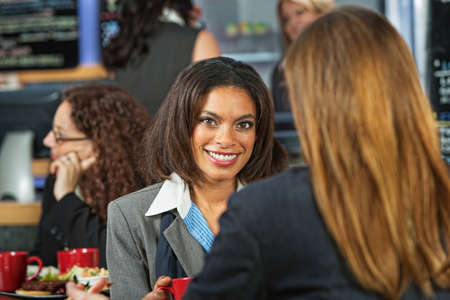 Smiling Black woman with coworker in cafeteria Фото со стока - 28505518