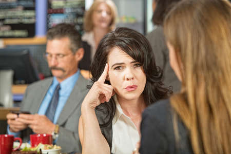 irked: Woman with finger on head and sitting with friend Stock Photo